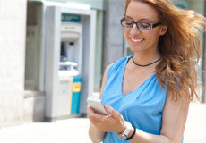 A woman with a blue blouse using a mobile phone