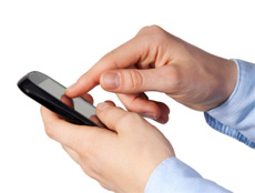 A man with a blue shirt, using a black cellphone