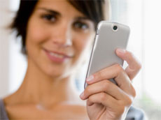 A woman showing her silver mobile phone