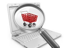 Red shopping cart, magnifying glass and a laptop