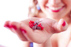 A woman holding red tacks on her hand