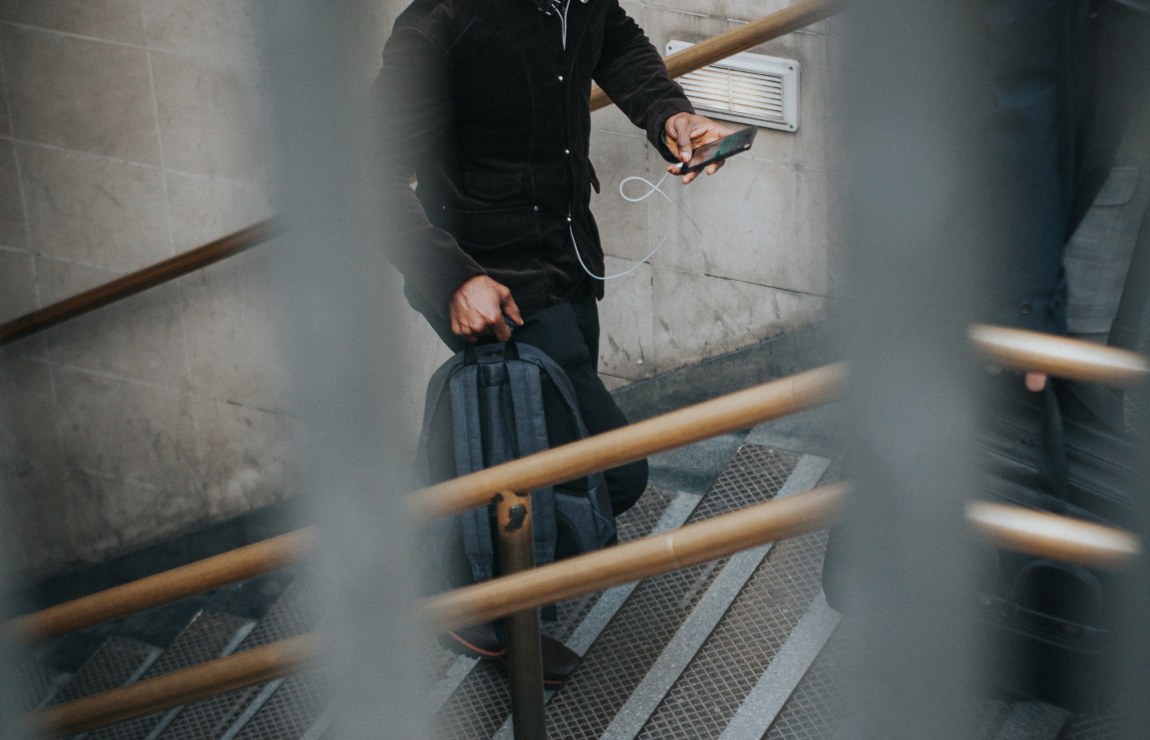Man walking up stairs while using smartphone