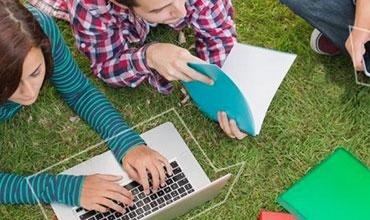Teenagers on the grass looking at their computers